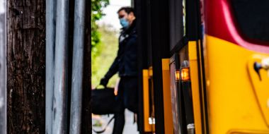 Man wearing face mask stepping off a bus